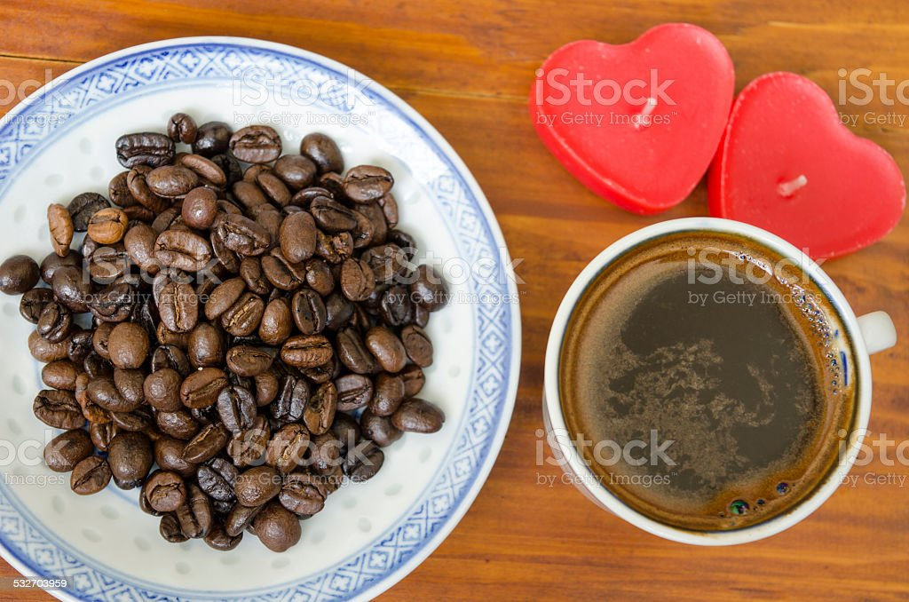 Coffee beans an cup of coffee on a wooden table royalty-free stock photo