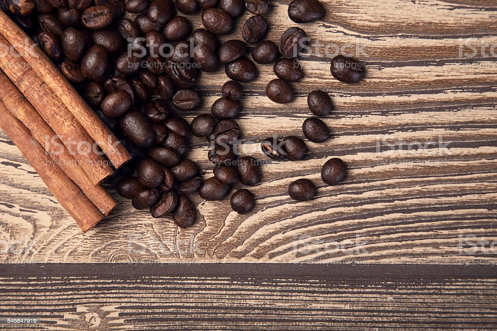 Coffee beans and cinnamon on wooden table. Top view. stock photo