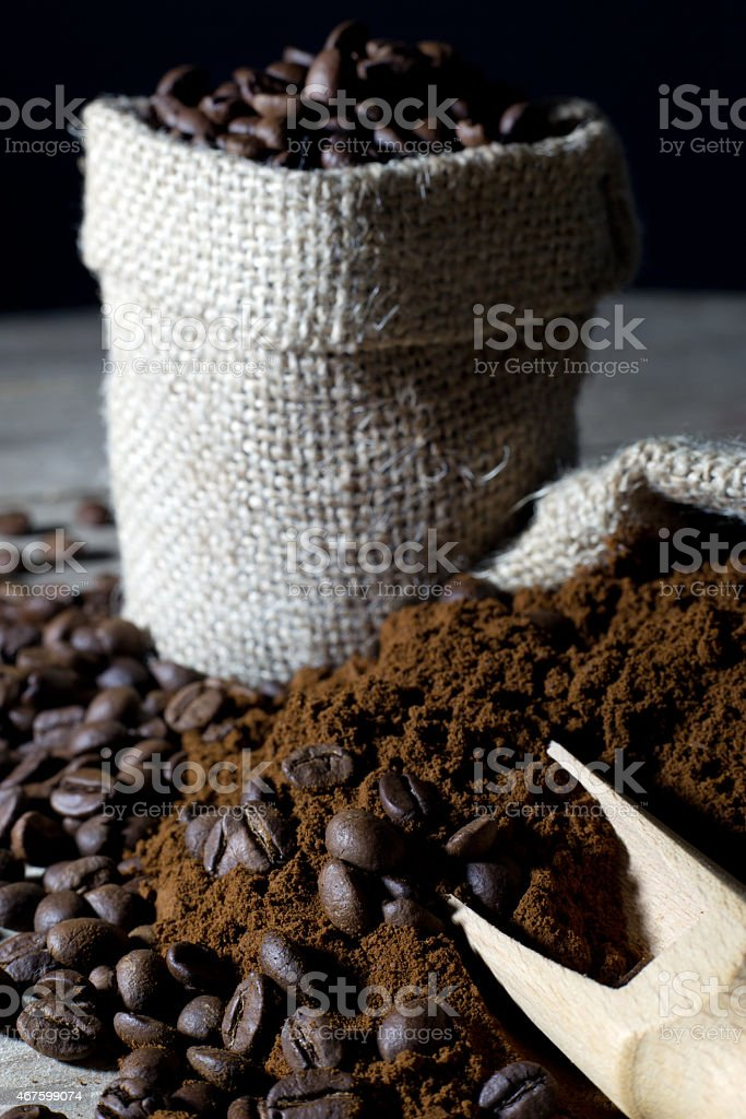 Coffee Beans and Ground Coffee with Wooden Scoop Closeup stock photo