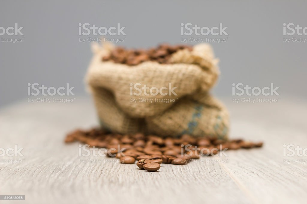 Coffee beans and textile sack on wooden table stock photo