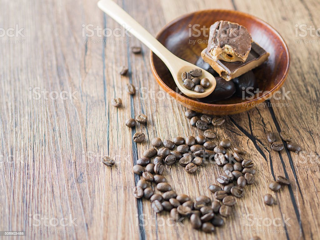 Coffee beans arranged heart figure with spoon and chocolate bars. royalty-free stock photo