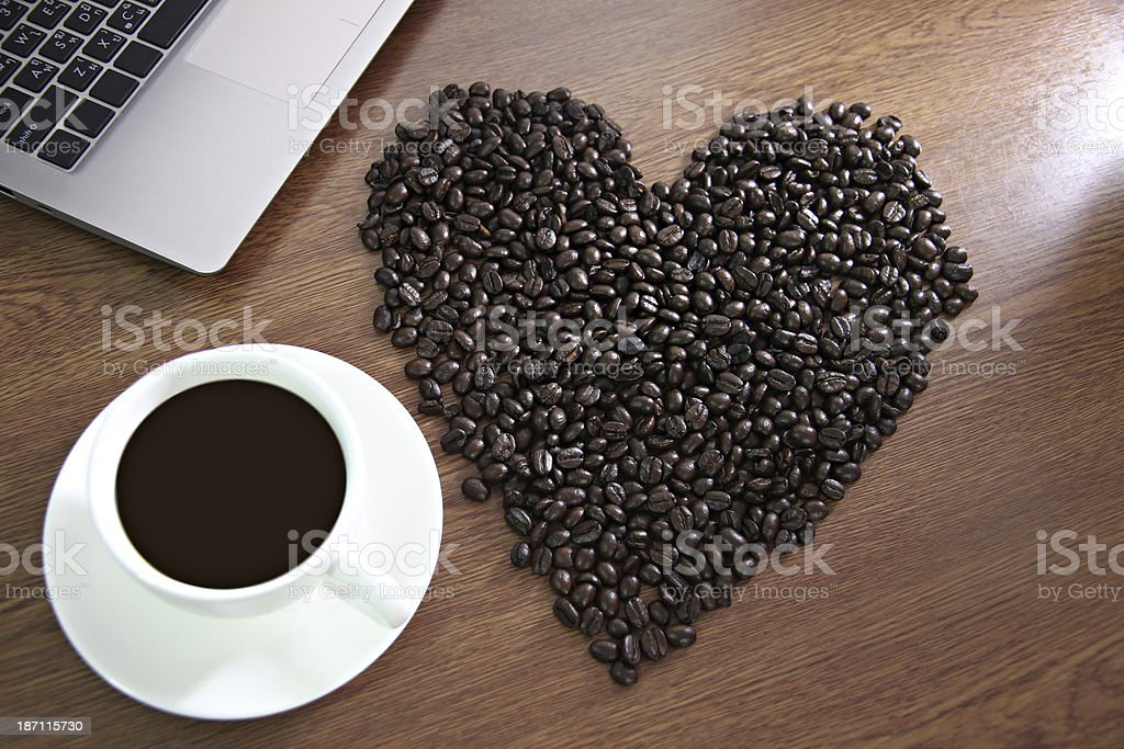 Coffee beans arranged shaped into a heart near white cup. royalty-free stock photo