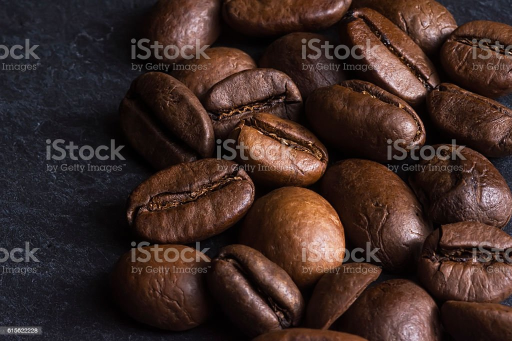 Coffee Beans Background. Roasted Coffee Beans on Dark Stone Surface. stock photo