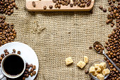 coffee beans, coffe cup on linen cloth background top view