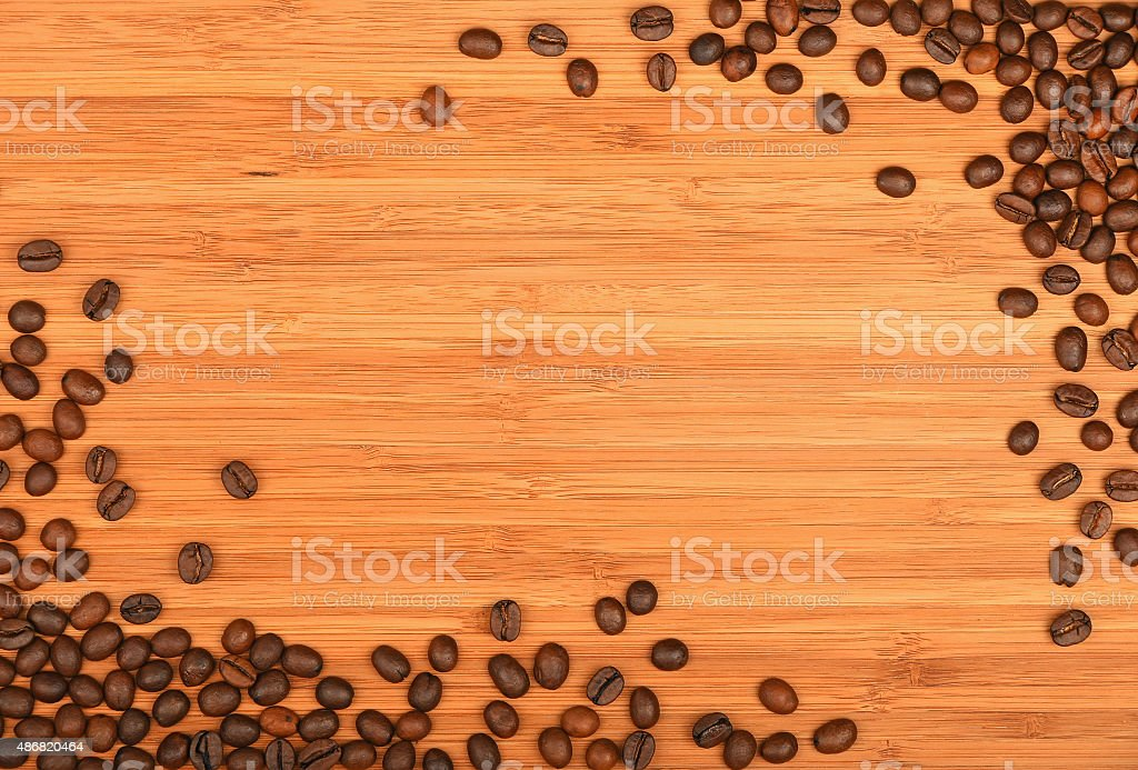 Coffee beans corners over bamboo wood background royalty-free stock photo