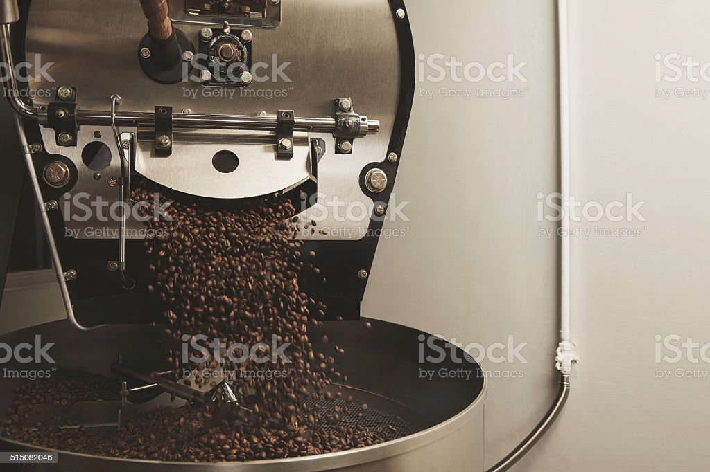 coffee beans fall from a large roaster machine stock photo