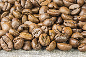 Coffee beans grunge wooden background on the table closeup side