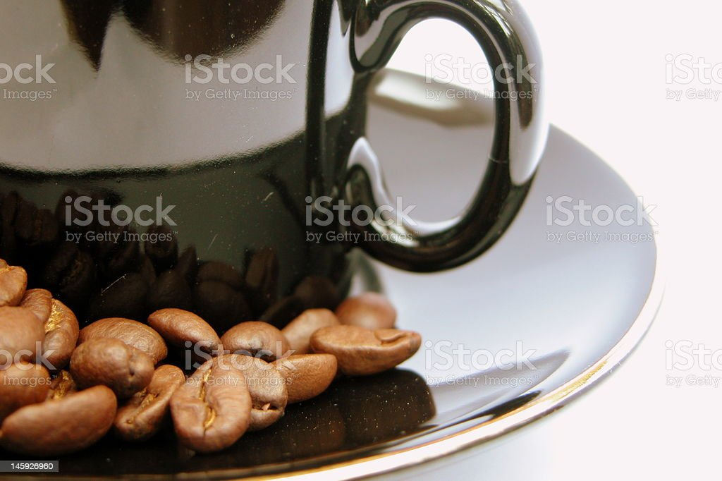 Coffee beans in a black glossy cup and saucer stock photo