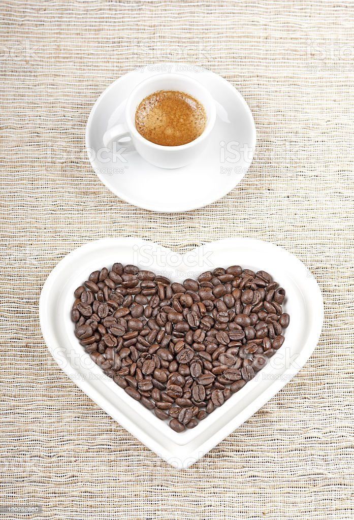 Coffee beans in a heart shaped bowl and espresso in a cup royalty-free stock photo