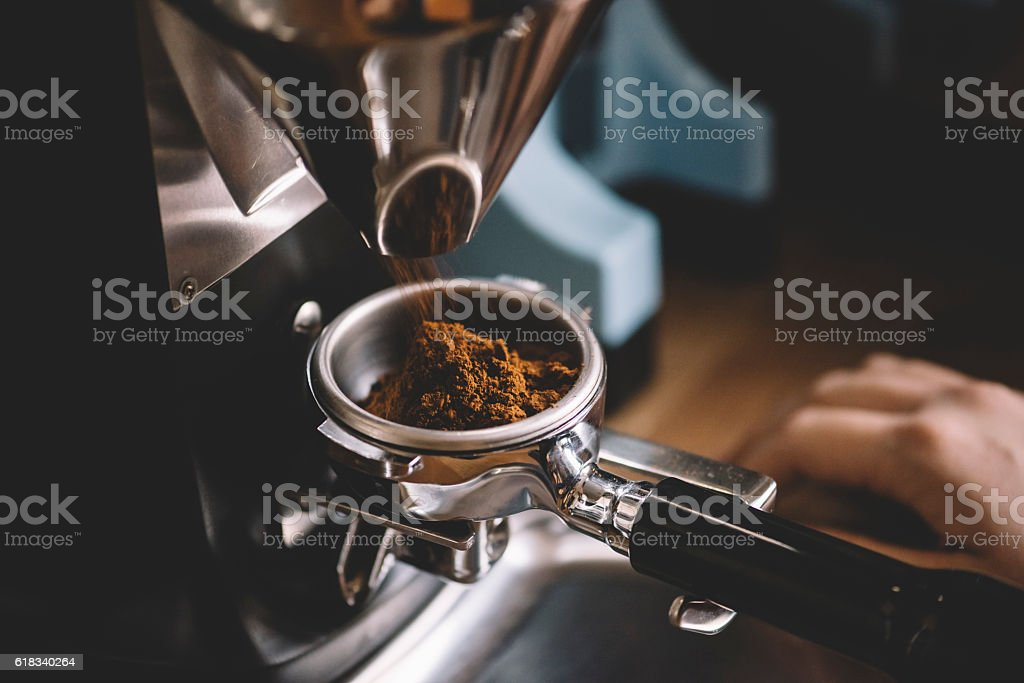 Coffee beans in a portafilter by the coffee grinder stock photo