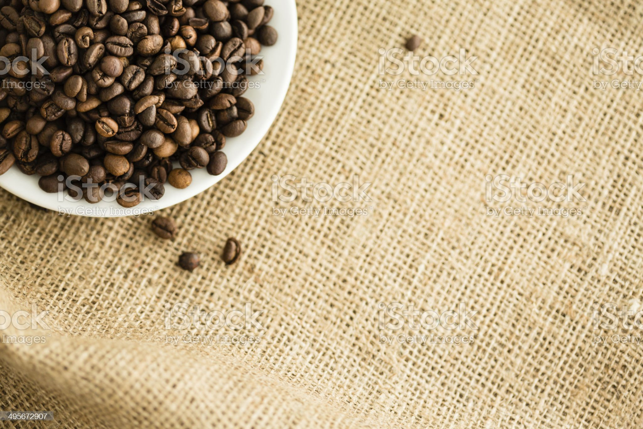 Coffee beans in a saucer on burlap royalty-free stock photo