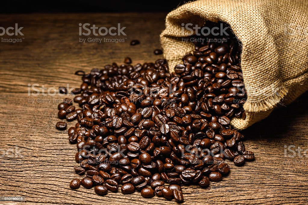 Coffee beans in bag made from burlap on wooden surface. stock photo