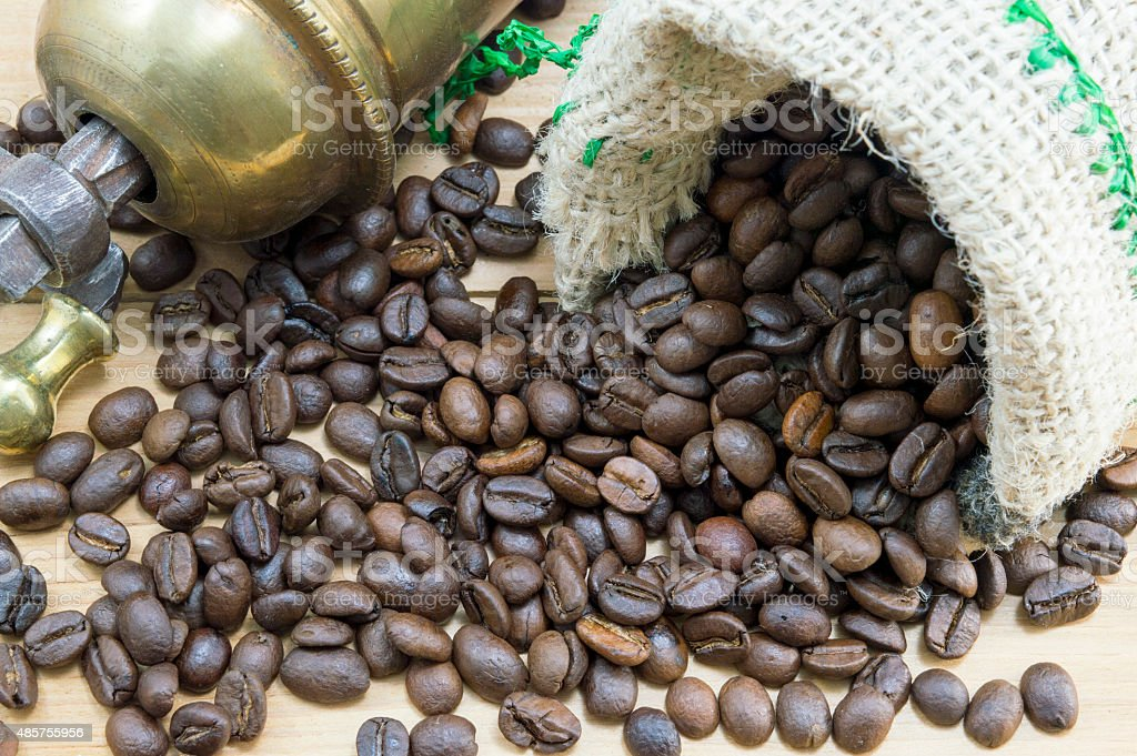 Coffee beans in coffee bag next to vintage coffee grinder stock photo