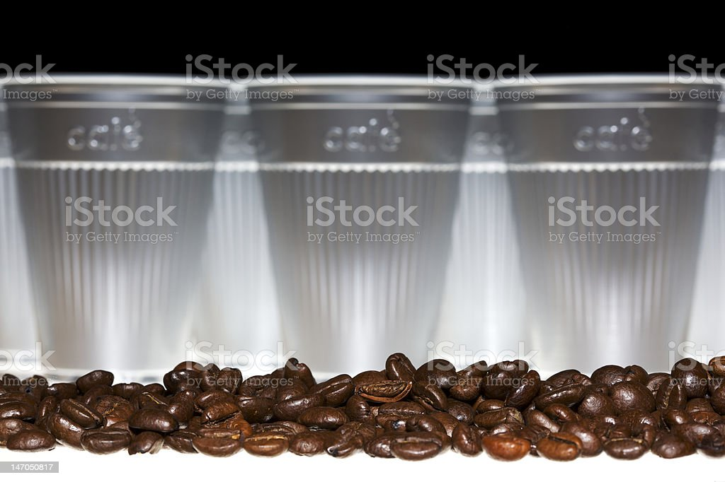 Coffee beans in front of plastic cups royalty-free stock photo