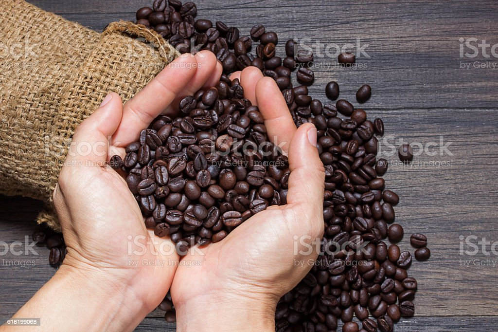 Coffee beans in hands on dark background stock photo