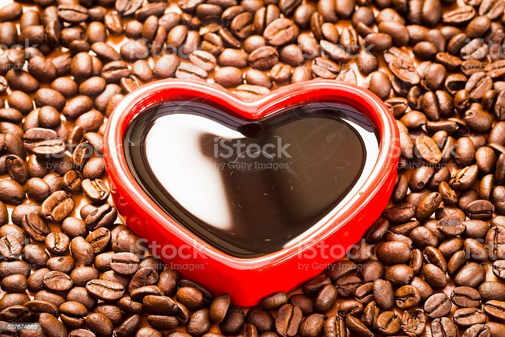 Coffee beans in red heart on wood background stock photo