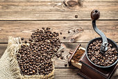 Coffee beans in sack and coffee grinder on wooden table