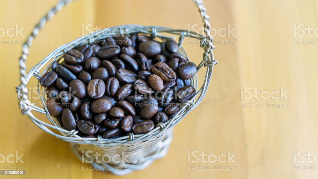 coffee beans in the basket on the wooden background. stock photo