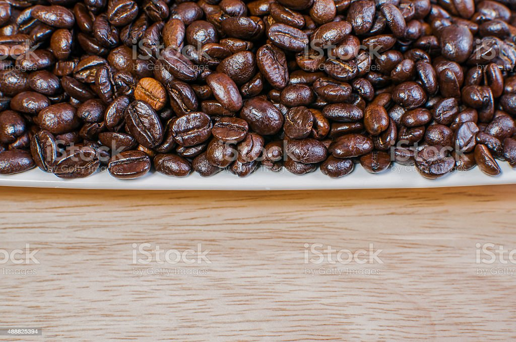 Coffee beans in white cup on the table stock photo
