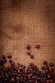 Coffee beans on burlpab background