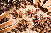Coffee beans on sackcloth with spices anise and cinnamon sticks