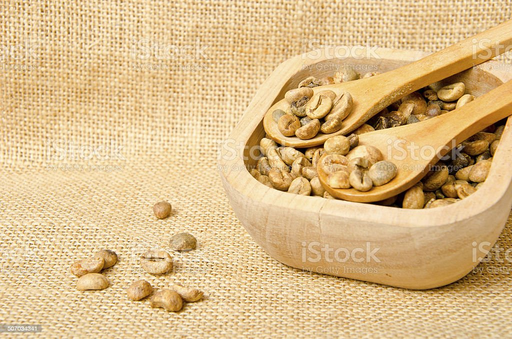 Coffee beans on wooden spoons and cup royalty-free stock photo