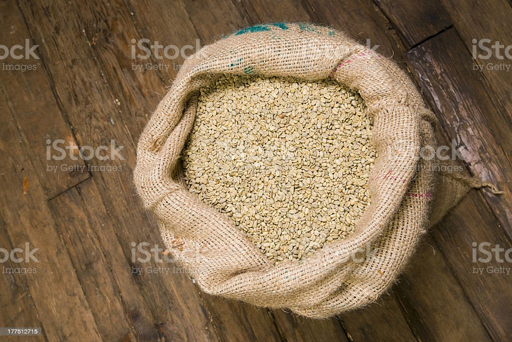 Coffee Beans Seeds Raw in Burlap Sack on Wood Floor royalty-free stock photo