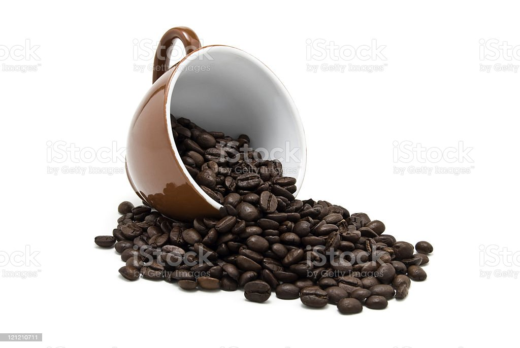 Coffee beans spilling from overturned brown mug stock photo