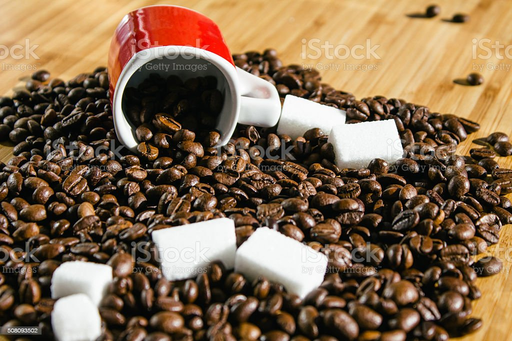 Coffee beans spilling out from a red cup stock photo