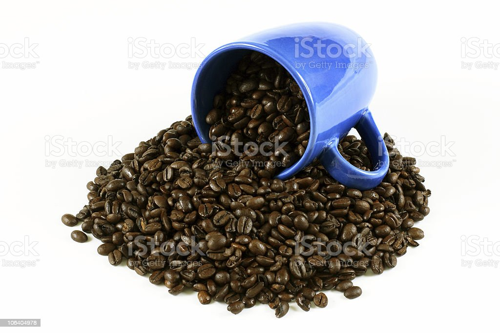 Coffee beans spilling out of a blue mug royalty-free stock photo