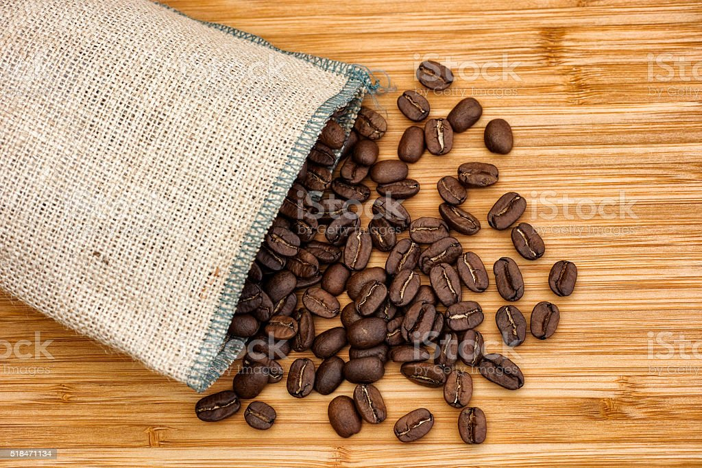 Coffee beans spilling out of burlap bag stock photo