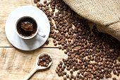 coffee beans with coffe cup on wooden table top view