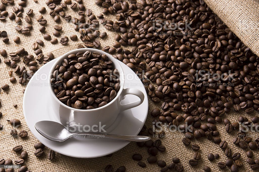 Coffee beans with cup and saucer royalty-free stock photo