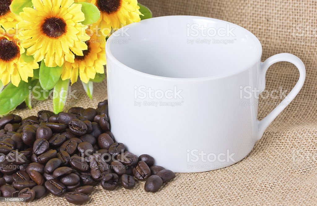 Coffee beans with cup on sackcloth. royalty-free stock photo