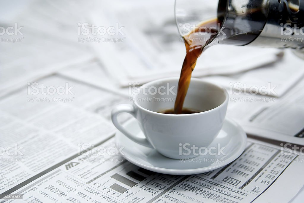 Coffee being poured into a cup on top of a newspaper stock photo