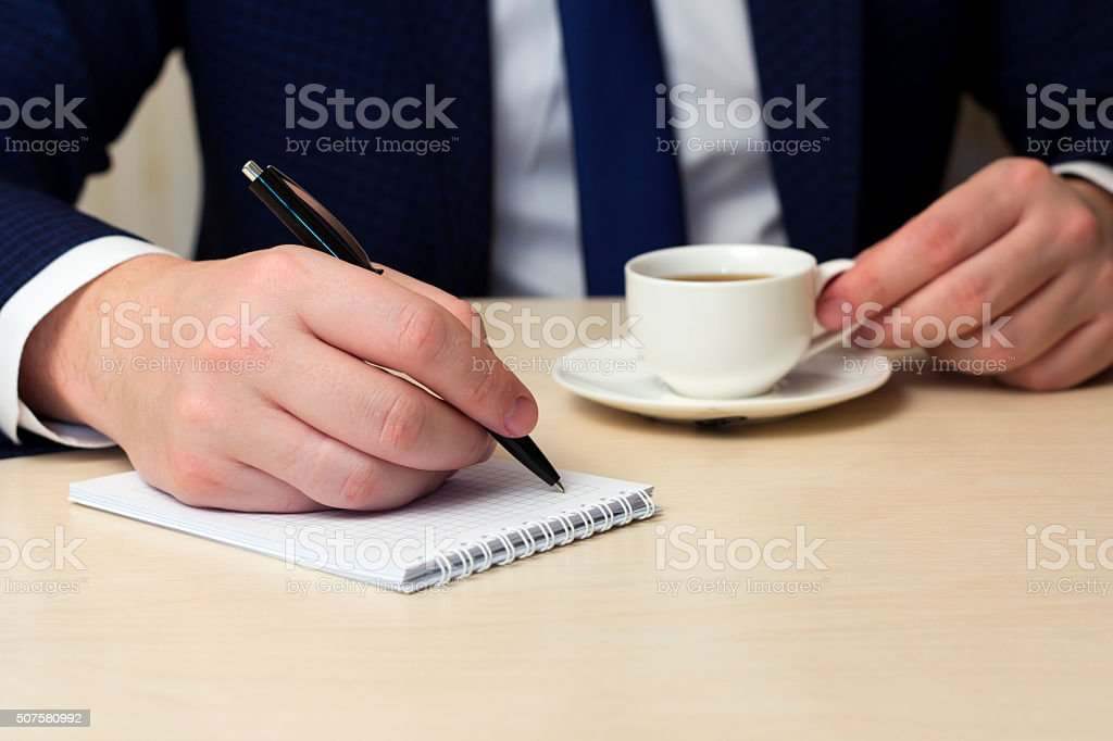 coffee break, a man at a table  makes record stock photo
