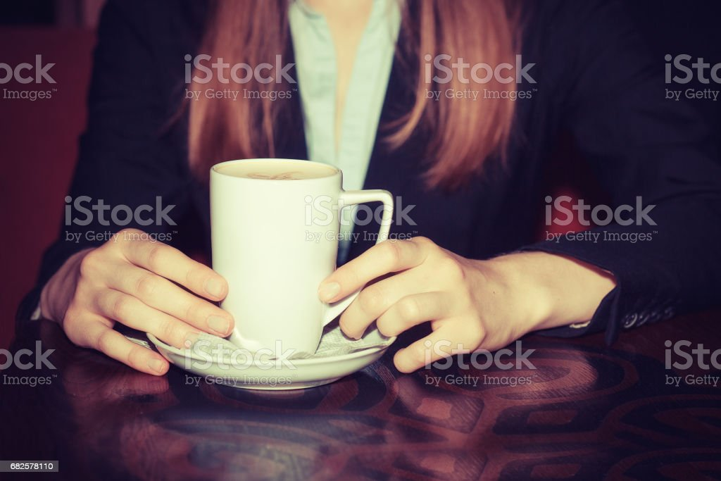 Coffee break. Close up portrait of female hands holding cups of hot beverage cappuccino latte mocha on rustic wooden table isolated on dark red background in fancy coffee shop, cafe. relaxation moment stock photo