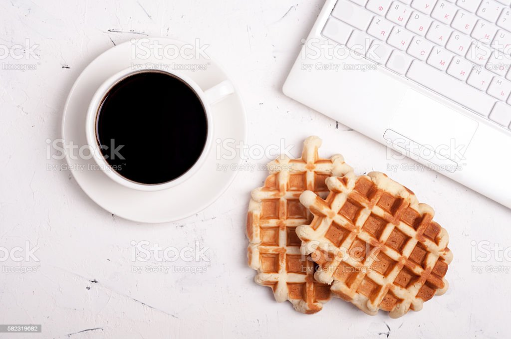Coffee break concept. Desk table with laptop, coffee cup, waffles stock photo