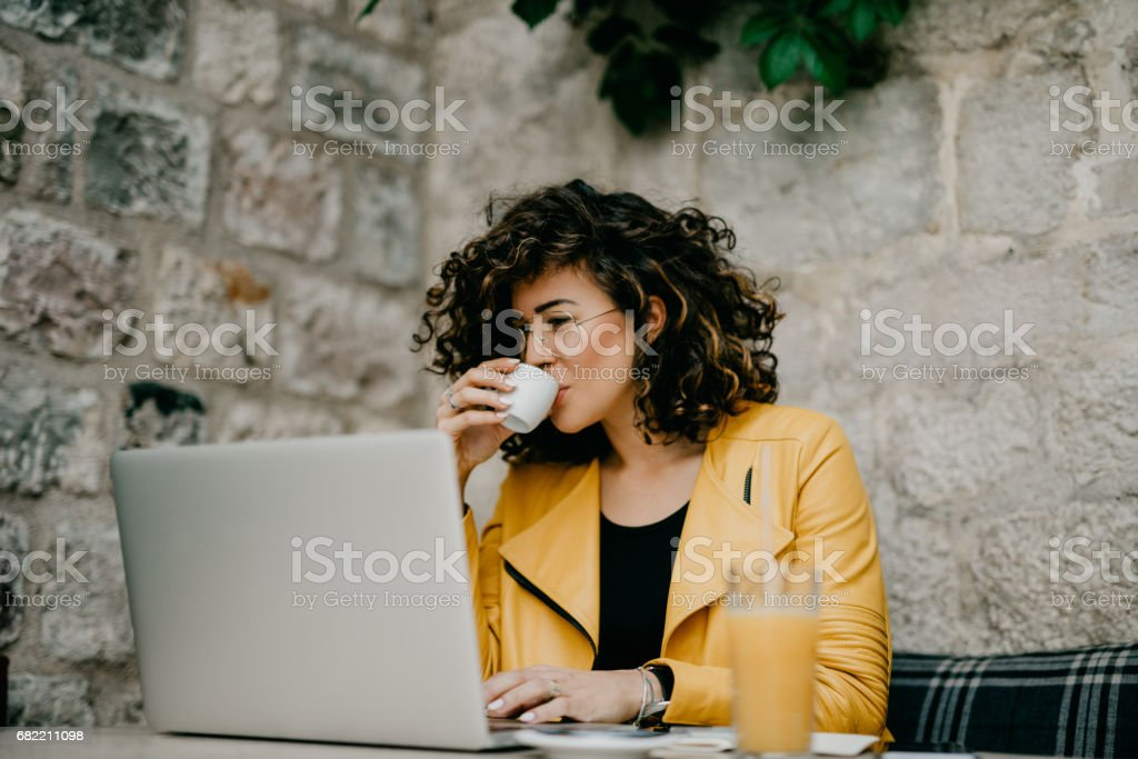 Coffee break for a beautiful curly-haired girl stock photo