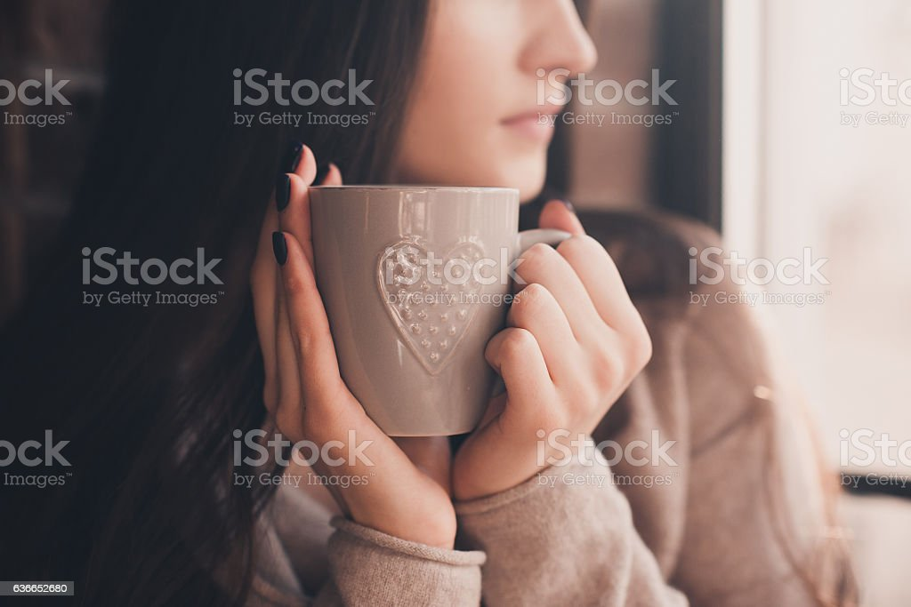 Brunette woman 20-24 year old holding ceramic cup of tea closeup....