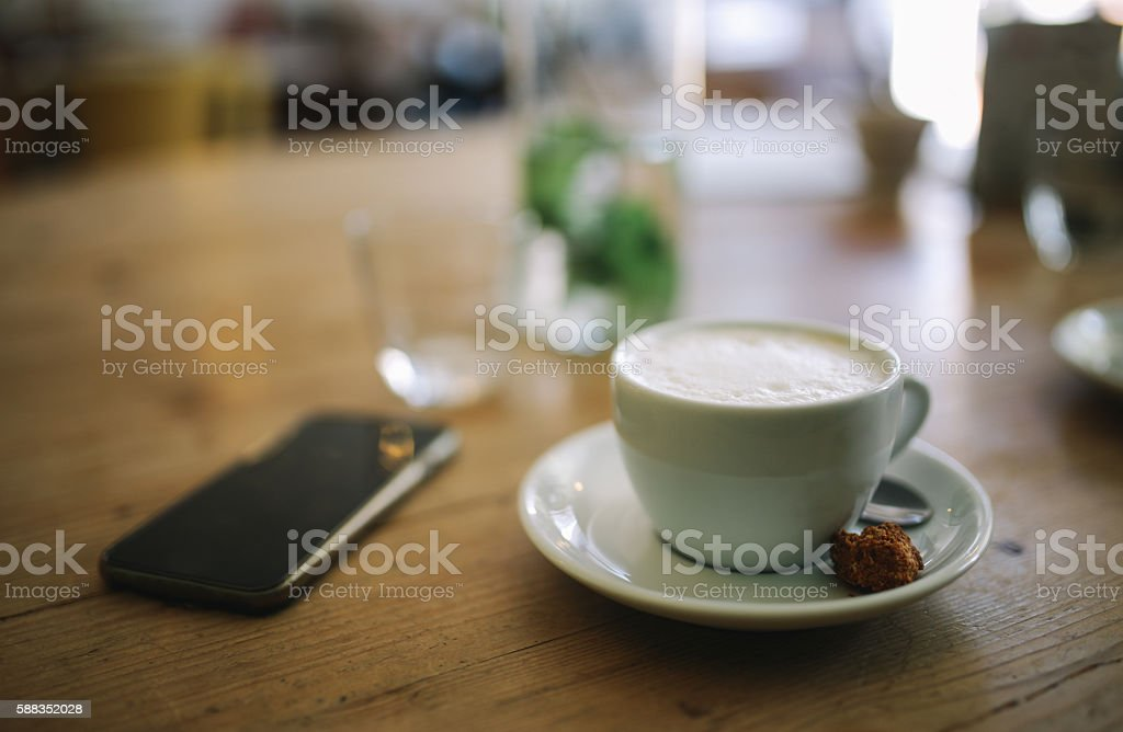 Vintage toned image of a cappuccino and a smartphone on the rustic...