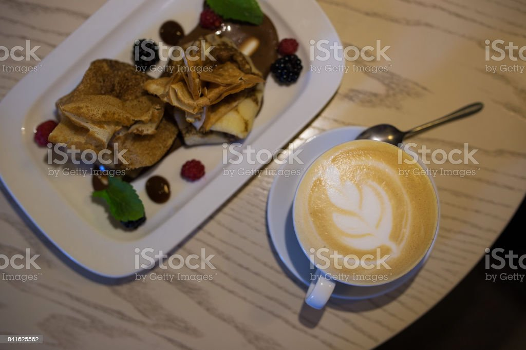 Coffee cappuccino in a coffee cup on wooden table and toast with ice cream stock photo