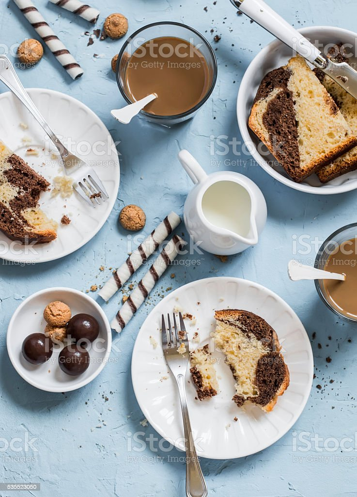 coffee, cookies, candy, cake, cream on a blue  background stock photo