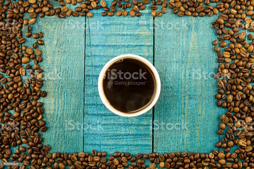 coffee Cup and beans on a blue wooden background stock photo