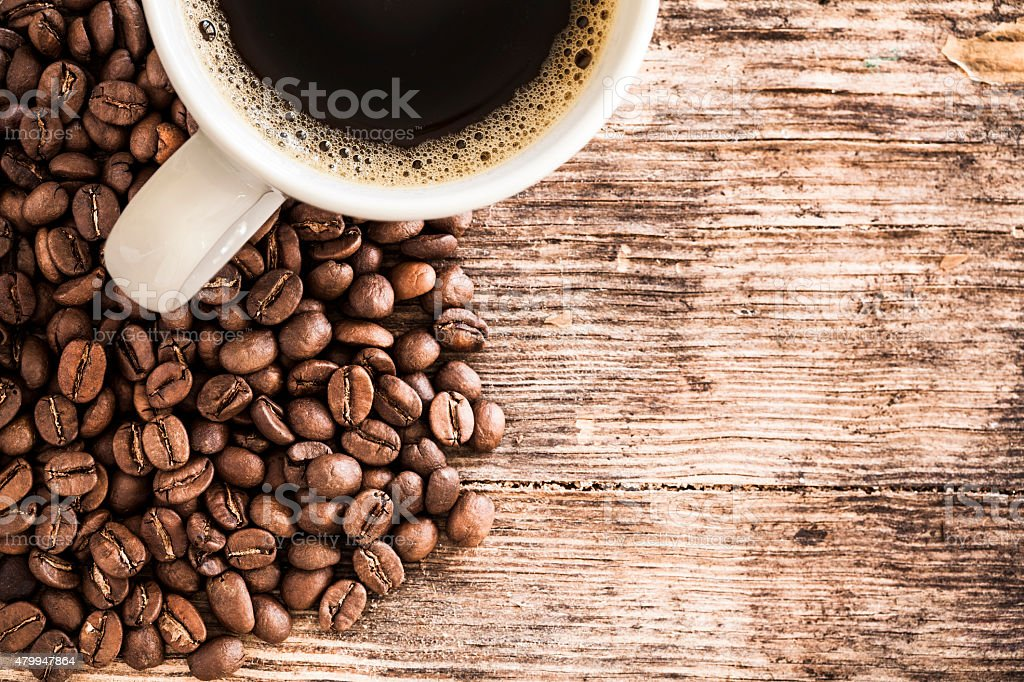 Coffee cup and beans on a wooden table stock photo