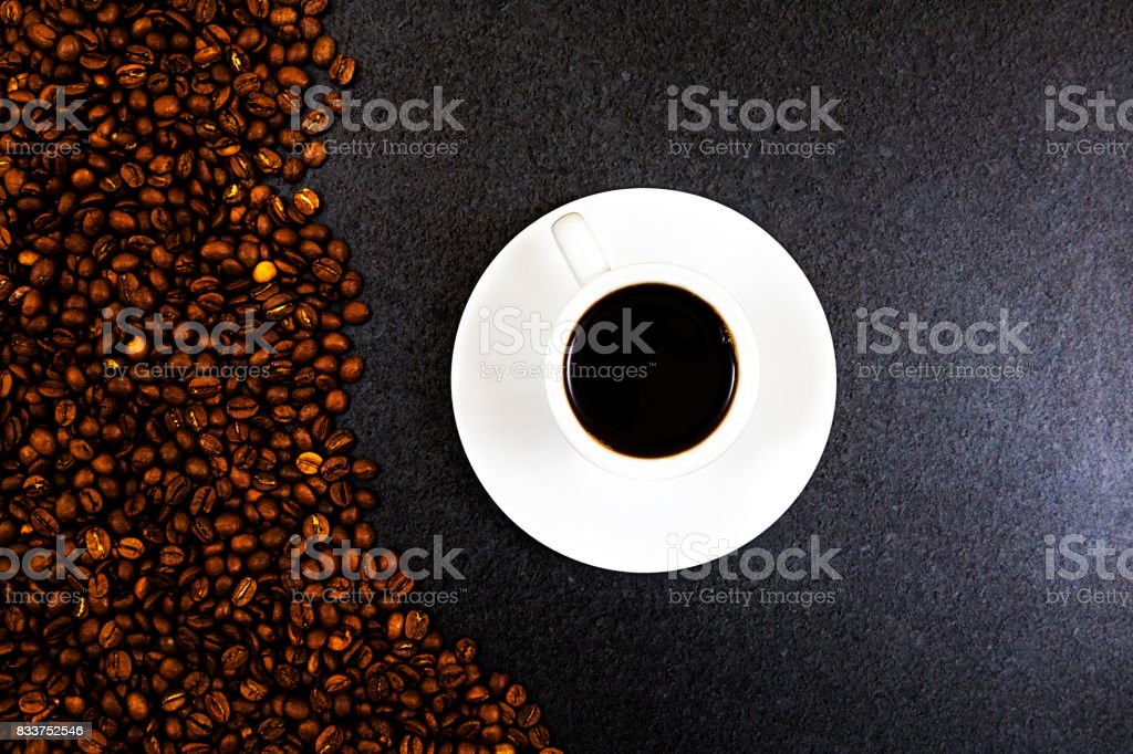 Coffee cup and beans on old kitchen table with copy space stock photo