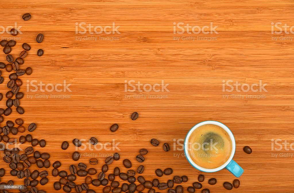 Coffee cup and beans over wood background royalty-free stock photo