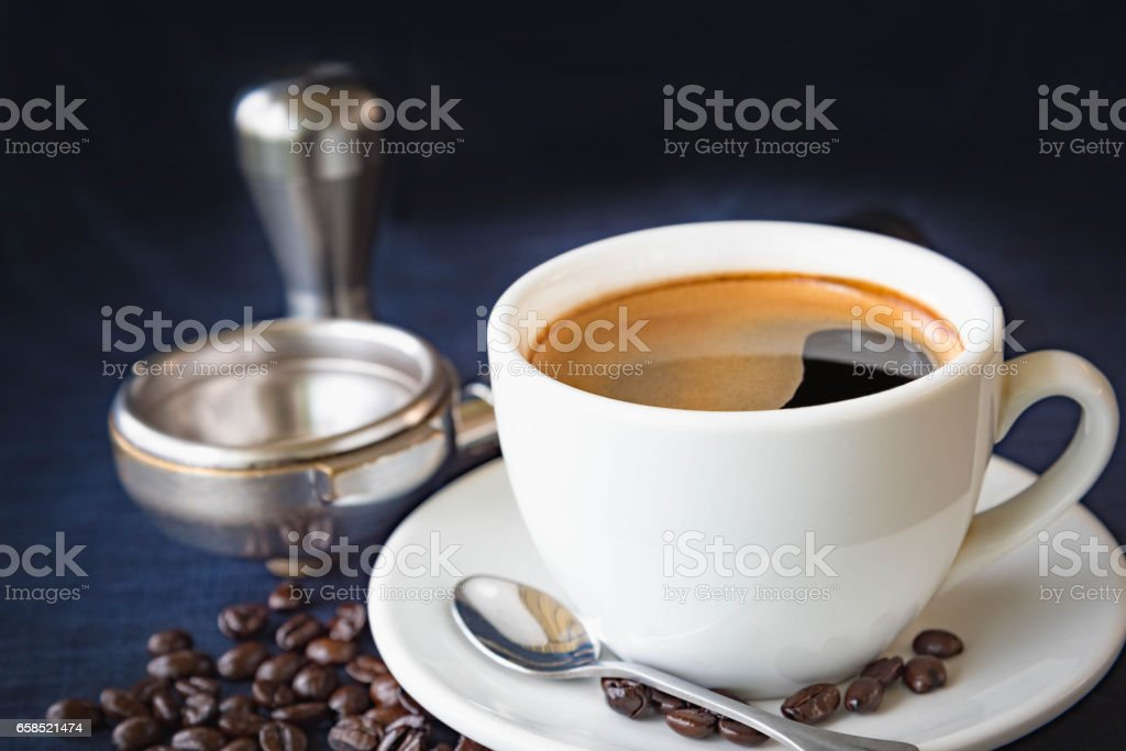 Coffee cup and beans with Equipment for coffee on a dark blue fabric...