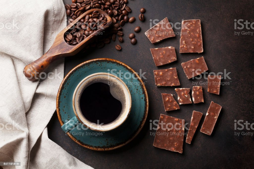 Coffee cup, beans and chocolate on old kitchen table. Top view