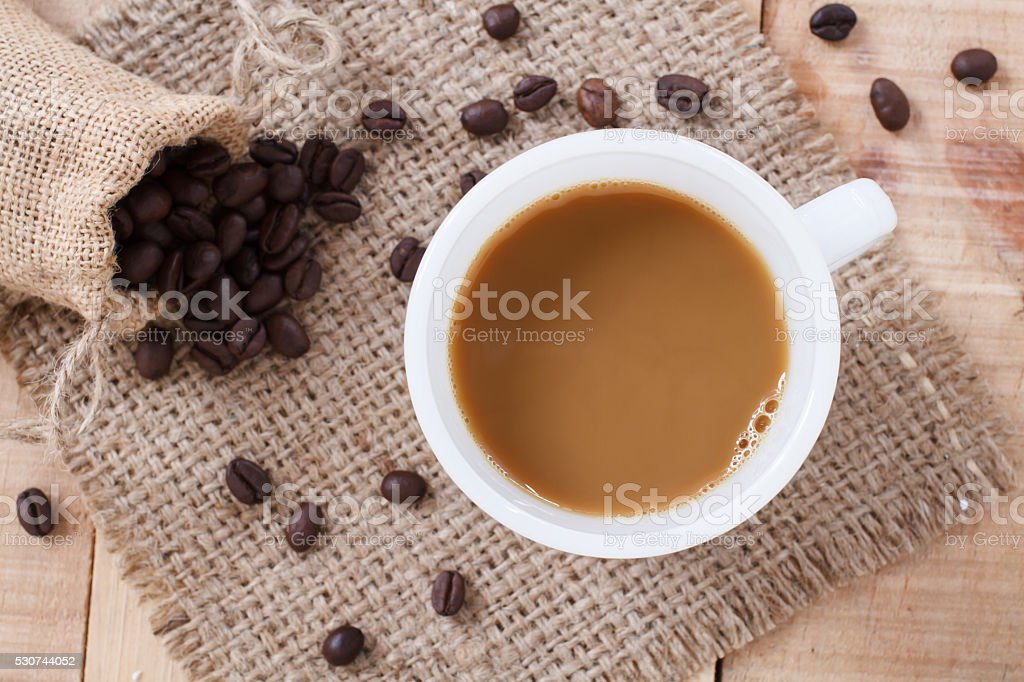 Coffee cup and coffee beans on sackcloth mat,Top view stock photo
